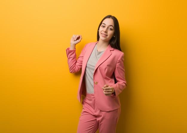 Joven mujer de negocios moderna bailando y divirtiéndose