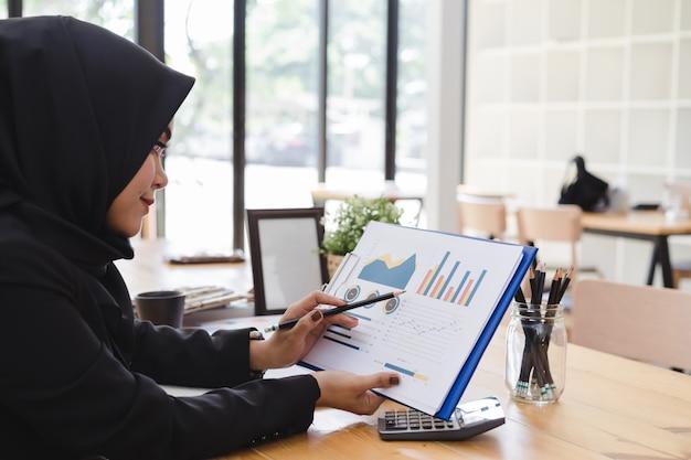 Joven mujer de negocios musulmana hijab negro informe comercial en coworking o cafetería.