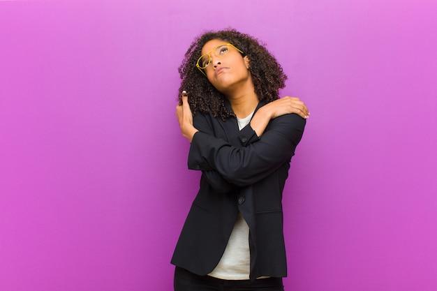 Joven mujer de negocios negra que se siente enamorada, sonriente, abrazada y abrazándose a sí misma, soltera, egoísta y egocéntrica