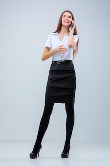 La joven mujer de negocios en la pared gris