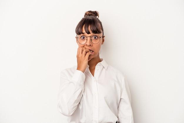 Joven mujer de negocios de raza mixta aislada sobre fondo blanco mordiéndose las uñas, nerviosa y muy ansiosa.