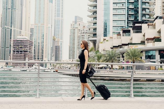 Joven mujer de negocios seguros modernos tirando de una maleta en un marine de dubai. comenzar un nuevo trabajo en una gran ciudad.