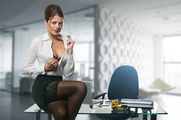 Joven mujer de negocios sexy en un escritorio en la oficina