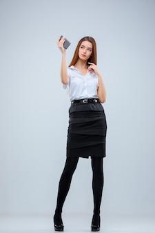 La joven mujer de negocios sobre fondo gris