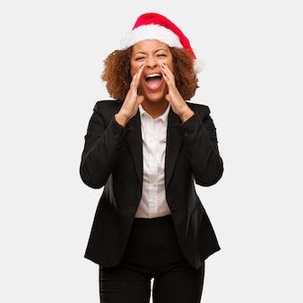 Joven mujer de negocios con un sombrero de santa chirstmas gritando algo feliz al frente