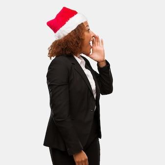 Joven mujer de negocios con un sombrero de santa chirstmas susurrando chisme bajo tono