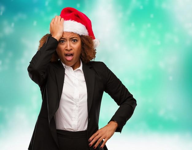 Joven mujer de negocios con un sombrero de santa de navidad preocupado y abrumado