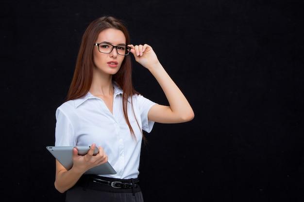 La joven mujer de negocios con tableta en pared negra