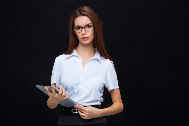 La joven mujer de negocios en vasos con tableta sobre un fondo negro