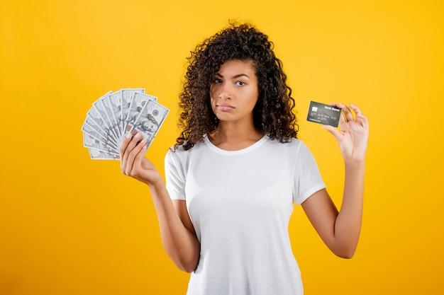 Joven mujer negra africana con dinero en dólares y tarjeta de crédito en mano aislado sobre amarillo