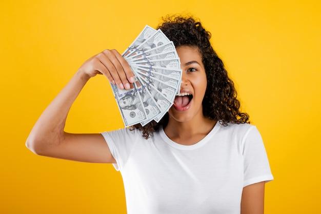 Joven mujer negra africana con dólares dinero en mano aislado sobre amarillo