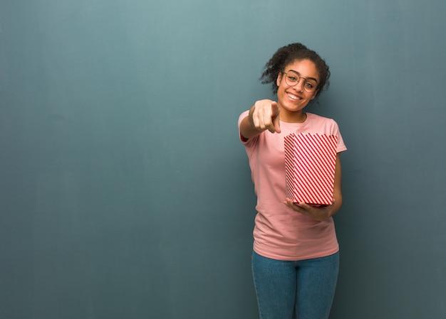 Joven mujer negra alegre y sonriente. ella está sosteniendo un cubo de palomitas de maíz.