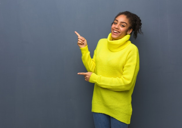 Joven mujer negra apuntando hacia el lado con el dedo