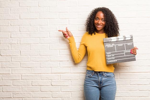 Joven mujer negra apuntando hacia un lado, sonriendo sorprendida presentando algo, natural e informal.