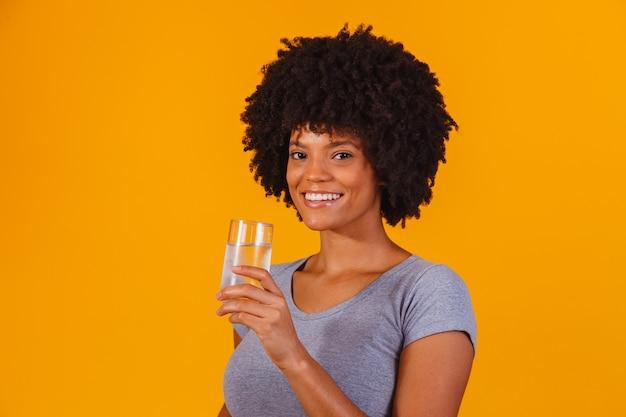 Joven mujer negra bebiendo agua en amarillo. niña joven, con, vaso de agua
