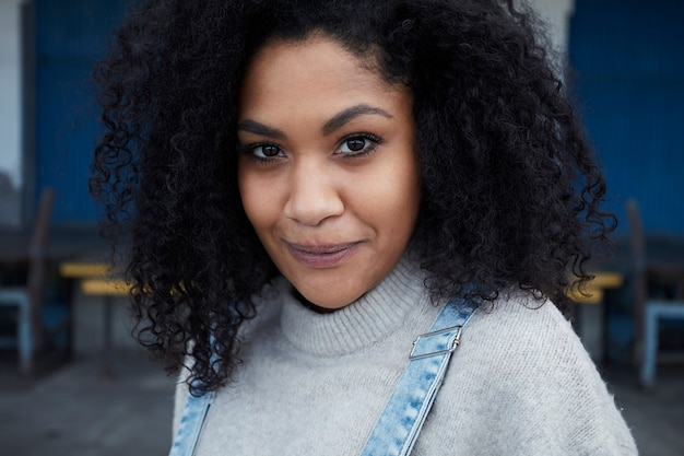 Joven mujer negra con cabello afro riendo y disfrutando