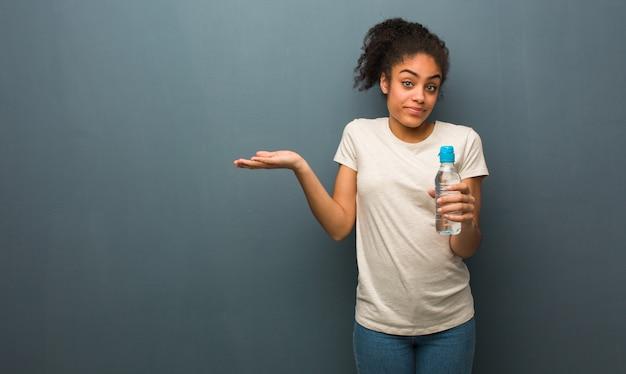 Joven mujer negra dudando y encogiéndose de hombros. ella está sosteniendo una botella de agua.