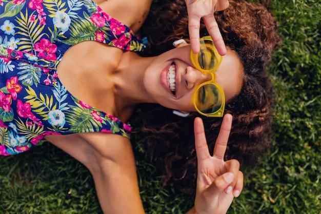 Joven mujer negra con estilo escuchando música con auriculares inalámbricos divirtiéndose tumbado en la hierba en el parque, estilo de moda de verano, traje de hipster colorido, vista desde arriba
