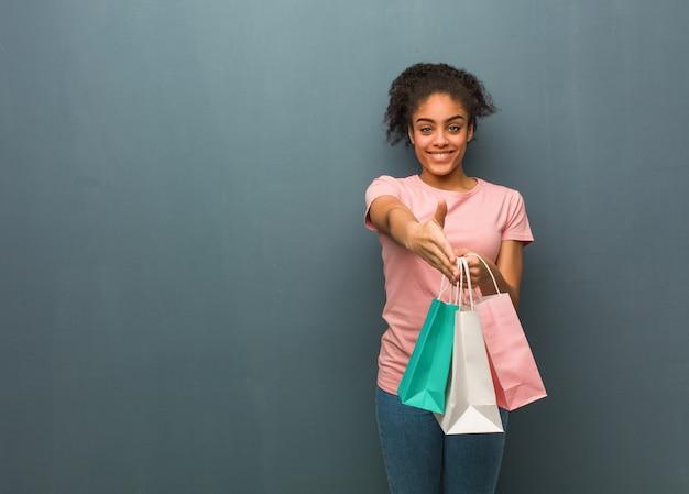 Joven mujer negra llegar a saludar a alguien. ella está sosteniendo una bolsa de compras.