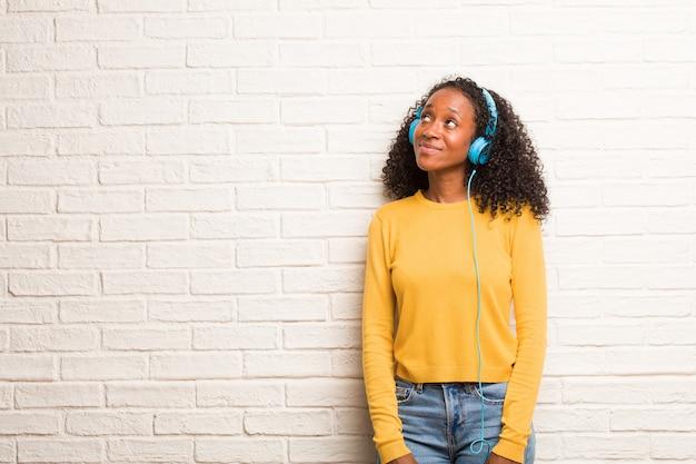 Joven mujer negra mirando hacia arriba, pensando en algo divertido y teniendo una idea, concepto de imaginación, feliz y emocionada.