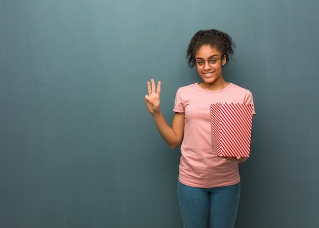 Joven mujer negra mostrando el número tres. ella está sosteniendo un cubo de palomitas de maíz.