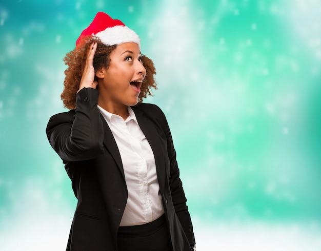 Joven mujer negra de negocios con un sombrero de santa chirstmas intenta escuchar un chisme