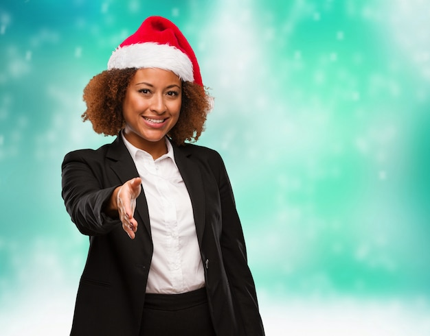 Joven mujer negra de negocios con un sombrero de santa chirstmas llegando a saludar a alguien