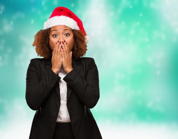 Joven mujer negra de negocios con un sombrero de santa chirstmas muy asustada y con miedo escondido