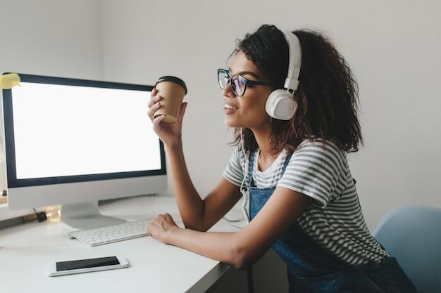 Joven mujer negra con nostalgia mirando a otro lado sosteniendo una taza de café y sonriendo mientras trabaja en la oficina