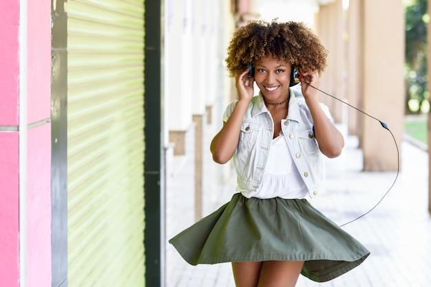 Joven mujer negra, peinado afro, en la calle urbana con auriculares