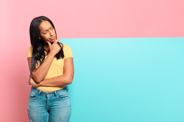 Joven mujer negra pensando, sintiéndose dudosa y confundida, con diferentes opciones, preguntándose qué decisión tomar. concepto de espacio de copia