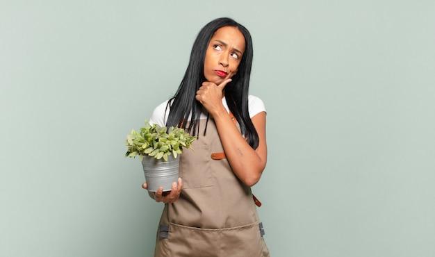 Joven mujer negra pensando, sintiéndose dudosa y confundida, con diferentes opciones, preguntándose qué decisión tomar. concepto de jardinero