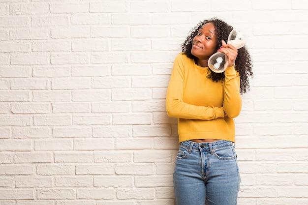 Joven mujer negra que duda y encoge de hombros, concepto de indecisión e inseguridad, insegura sobre algo.