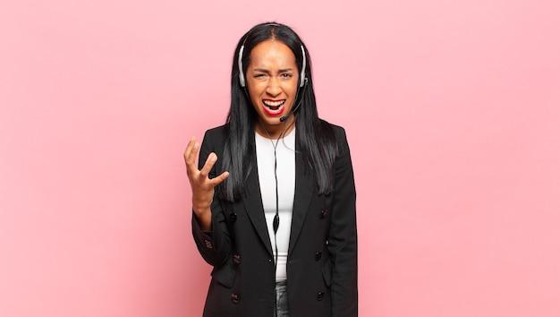 Joven mujer negra que parece enojada, molesta y frustrada gritando. concepto de telemarketing