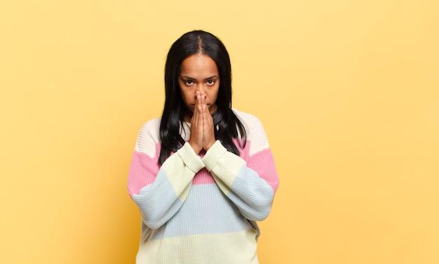 Joven mujer negra que se siente preocupada, esperanzada y religiosa, orando fielmente con las palmas presionadas, pidiendo perdón