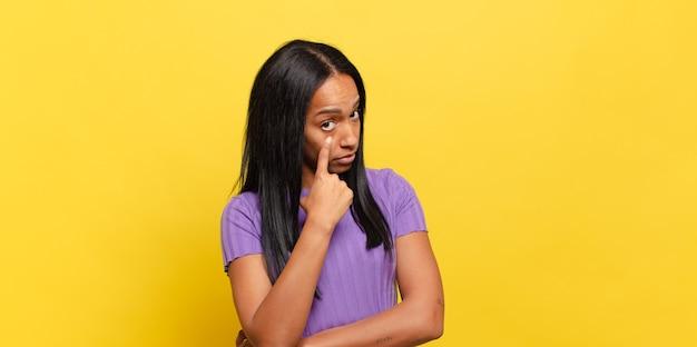 Joven mujer negra que te vigila, no confía, mira y permanece alerta y vigilante
