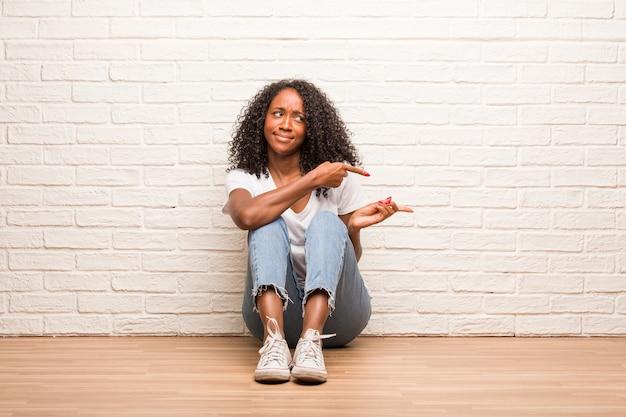 Joven mujer negra sentada en un piso de madera confundida y dudosa, decide entre dos opciones, concepto de indecisión