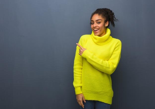 Joven mujer negra sonriendo y apuntando hacia el lado