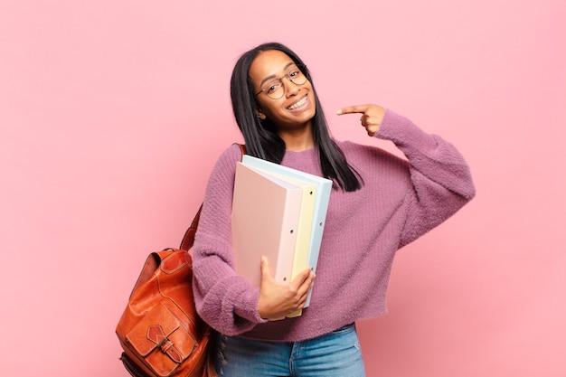 Joven mujer negra sonriendo con confianza apuntando a su propia sonrisa amplia, actitud positiva, relajada y satisfecha. concepto de estudiante