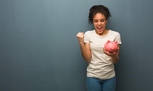 Joven mujer negra sorprendida y conmocionada. ella está sosteniendo una alcancía.