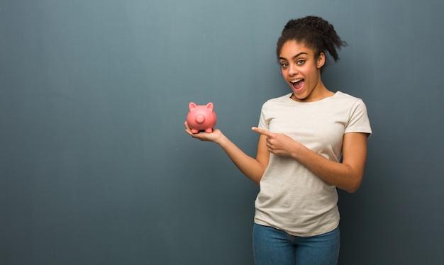 Joven mujer negra sosteniendo algo con la mano. ella está sosteniendo una alcancía.