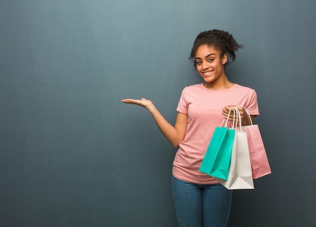 Joven mujer negra sosteniendo algo con la mano. ella está sosteniendo una bolsa de compras.