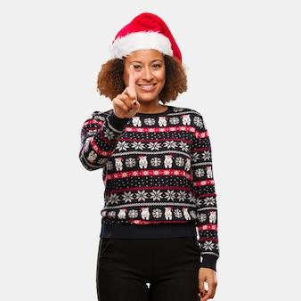 Joven mujer negra en un suéter de navidad de moda con estampado que muestra el número uno