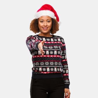 Joven mujer negra en un suéter navideño de moda con estampado que se extiende para saludar a alguien