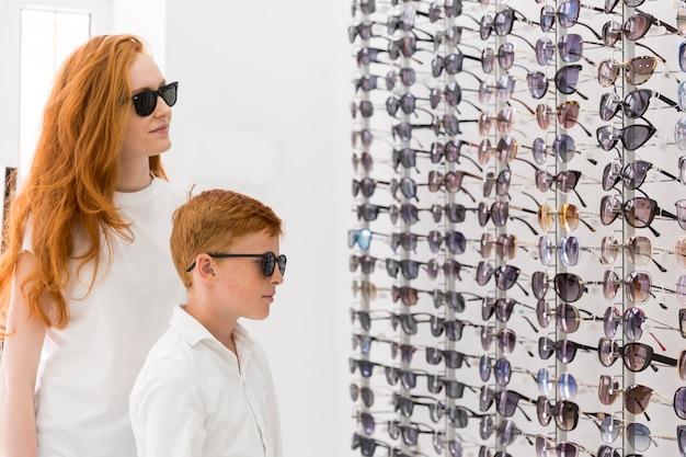 Joven mujer y niño de pie juntos en el showroom de óptica