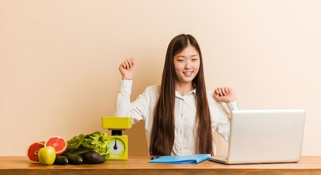 Joven mujer nutricionista china trabajando con su laptop bailando y divirtiéndose.