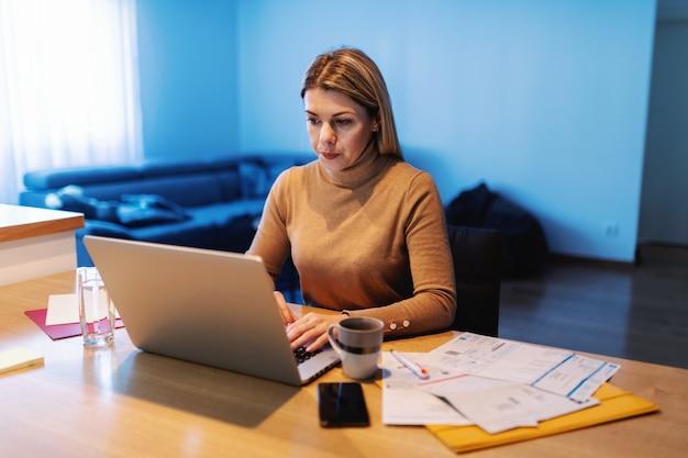 Joven mujer ocupada sentada en casa, usando la computadora portátil y trabajando en un proyecto importante. hay papeles, documentos sobre la mesa.