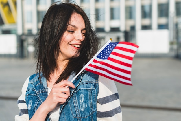Joven mujer ondeando bandera de estados unidos el cuatro de julio