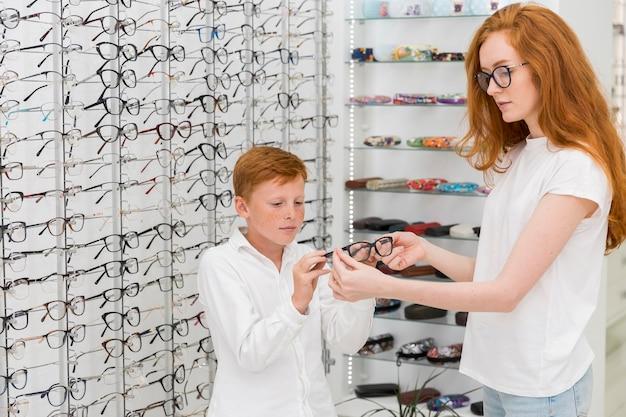 Joven mujer óptica mostrando espectáculo al niño en la tienda de óptica