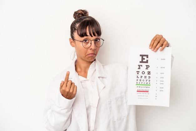 Joven mujer óptica de raza mixta haciendo una prueba aislada sobre fondo blanco apuntando con el dedo como si invitara a acercarse.